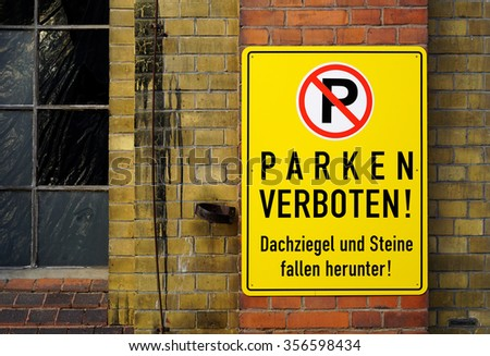 german sign that says No parking, roof tiles and stones fall down - stock photo