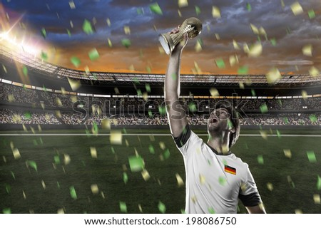 German soccer player, celebrating the championship with a trophy in his hand. - stock photo