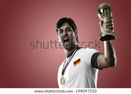 German soccer player, celebrating the championship with a trophy in his hand. On a red background. - stock photo