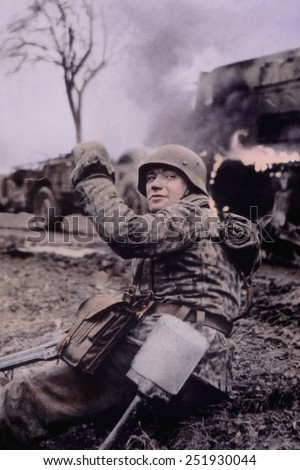 German soldier waving members of unit forward in the first days of the Battle of the Bulge. In the background are burning U.S. vehicles. Dec. 16-22, 1944. Belgium. B&W Photo with oil color. - stock photo