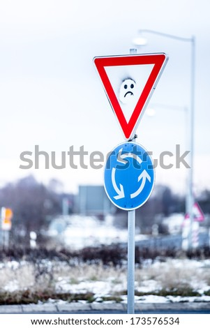 German traffic signs: roundabout traffic and yield sign  -  painted with smily  - stock photo