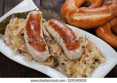 German white sausage or wurst served with sauerkraut and pretzel - stock photo