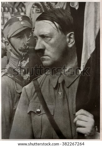 GERMANY - 1935:  Adolf Hitler holds a standard during the Party Congress of the NSDAP in Weimar Republic.  Reproduction of antique photo. - stock photo