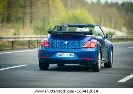 GERMANY - APRIL 3: VW Beetle cabriolet on German Autobahn on April 3, 2014 in Germany. Volkswagen is a German automobile manufacturer and the biggest German automaker. - stock photo