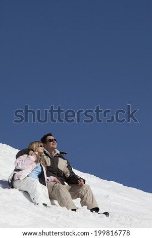 Germany, Bavaria, Couple in winter clothes sitting in the snow - stock photo