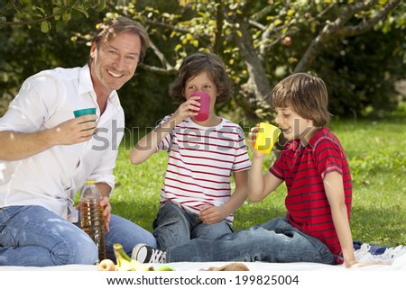 Germany, Bavaria, Father and children having drink at picnic
