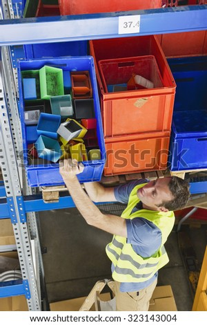 Germany,Bavaria,Munich,Manual worker working in warehouse - stock photo
