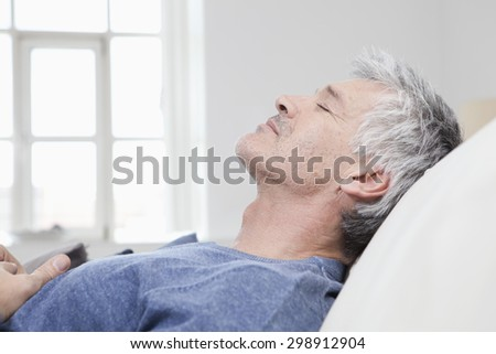 Germany, Bavaria, Munich, Mature man relaxing on sofa