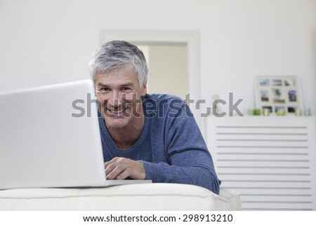Germany, Bavaria, Munich, Portrait of mature man using laptop on couch, smiling