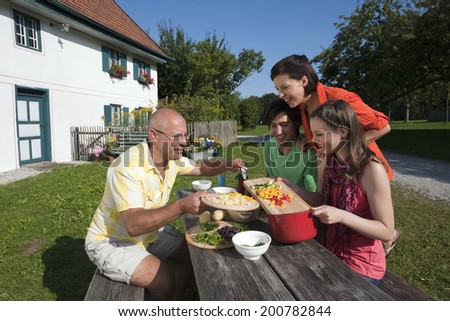 Germany, Bavaria, Two men and two women at table in garden preparing food - stock photo