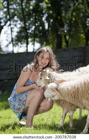 Germany, Bavaria, Young woman feeding sheep