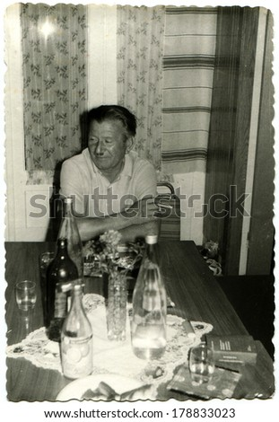 GERMANY, BERLIN - CIRCA 1960s: An antique photo of man with a cigarette in his hand sitting in front of a coffee table, cluttered with bottles of alcohol, Berlin