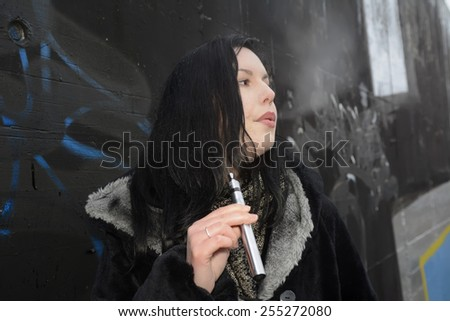 Germany, Berlin, young woman with e-cigarette - stock photo