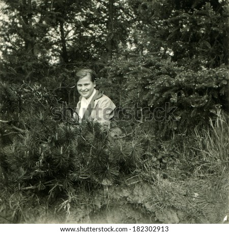 GERMANY, BRINCKMANSDORF - CIRCA 1950s: An antique photo of young woman posing among spruces