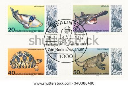 GERMANY - CIRCA 1977: A postmark shows Paddlefish, Tortoise, Rhinoceros iguana, chimpanzee and statue of iguanodon from Aquarium entrance, 25th anniv. of the reopening of Berlin Aquarium, circa 1977 - stock photo
