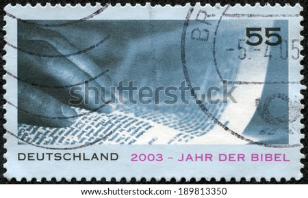 GERMANY - CIRCA 2003: A stamp printed in German Federal Republic issued for Year of the Bible, showsHand and Page, circa 2003