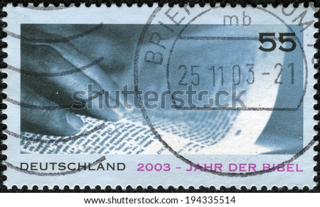 GERMANY - CIRCA 2003: A stamp printed in German Federal Republic issued for Year of the Bible, showsHand and Page, circa 2003 - stock photo