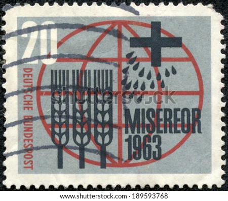 GERMANY - CIRCA 1963: a stamp printed in the Germany shows Globe, Cross, Seeds and Stalks of Wheat, German Catholic Campaign against Hunger and Illness, circa 1963 - stock photo