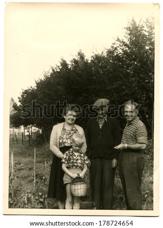 GERMANY - CIRCA 1962: An antique photo of two mature men and a woman, a little boy with a basket on the background of the garden,