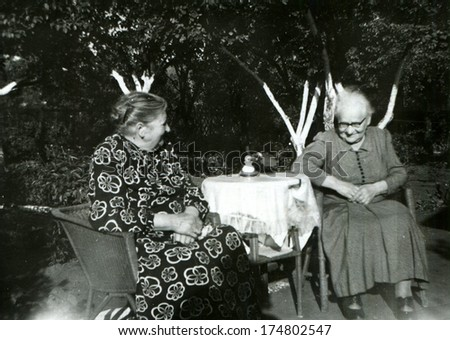 GERMANY -  CIRCA 1953: An antique photo shows two old women talking at the round table in the garden