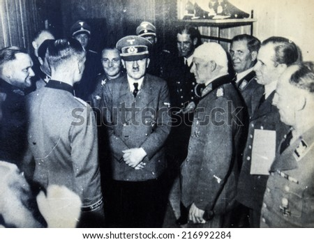 GERMANY - CIRCA 1940s: Adolf Hitler among the officers, one of whom is bandaged head. Reproduction of antique photo. - stock photo