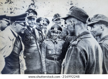 GERMANY - CIRCA 1940s: Adolf Hitler surrounded by officers talking to a soldier. Reproduction of antique photo. - stock photo