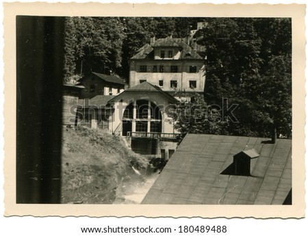 GERMANY - CIRCA 1960s: An antique photo of view from the window of a neighboring building on a background of mountain forest - stock photo