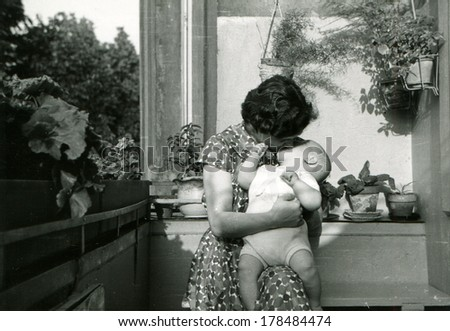 GERMANY - CIRCA 1960s: An antique photo of woman kisses a child sitting on the balcony