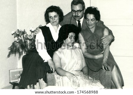 GERMANY -  CIRCA 1970s: An antique photo shows man in glasses posing with three women