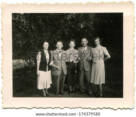GERMANY -  CIRCA 1930s: An antique photo shows two men and three women posing in the garden