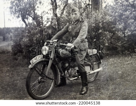 GERMANY - CIRCA 1940s: German soldiers posing on a motorcycle, Germany, 1940s. Reproduction of antique photo.