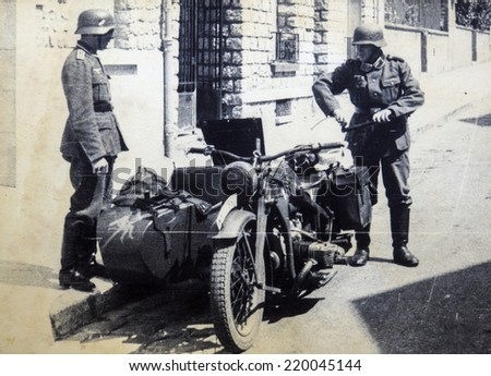 GERMANY - CIRCA 1940s: German soldiers posing on a motorcycle, Germany, 1940s. Reproduction of antique photo. - stock photo