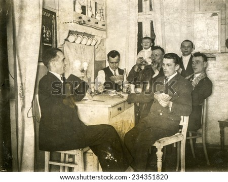 GERMANY, CIRCA 1920s: Vintage photo of group of men playing cards - stock photo