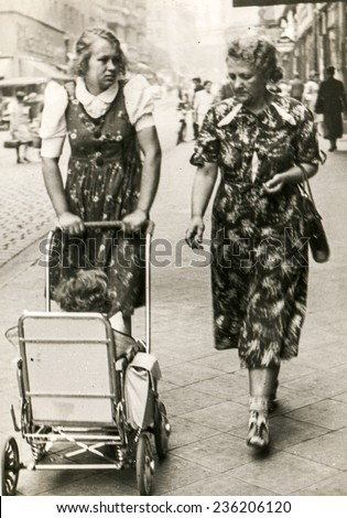 GERMANY, CIRCA 1940s: Vintage photo of two women walking dawn the street with a baby in pram - stock photo