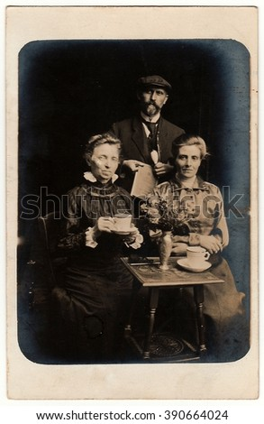 GERMANY - CIRCA 1910s: Vintage photo shows man and women pose with a cup, newspaper and pipe. Antique black & white studio portrait.