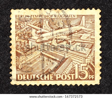 GERMANY - CIRCA 1949: Stamp printed in Germany with caricature of a Douglas C-54 Skymaster airplane over Berlin Tempelhof airport, circa 1949.
