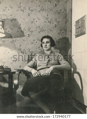 GERMANY, CIRCA THIRTIES - Vintage portrait of woman sitting by masonry heater