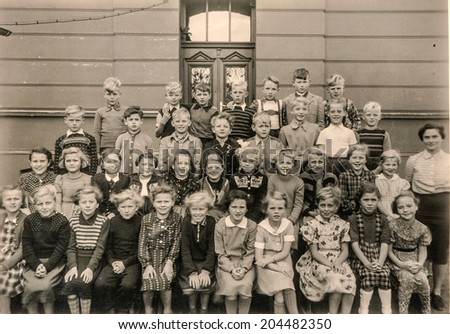 GERMANY, CIRCA 1953 - Vintage photo of group of schoolmates and teacher posing in front of their school - stock photo
