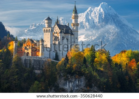 Germany. Famous Neuschwanstein Castle in the background of snowy mountains and trees with yellow and green leaves. - stock photo