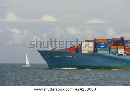 GERMANY, HAMBURG, CUXHAVEN, 2012-07-16:  Outbound Container-ship passing a small sailing boat in mouth of river Elbe near Cuxhaven