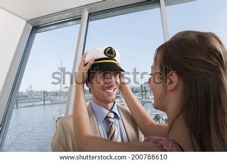 Germany, Hamburg, Woman putting sailor's cap on man - stock photo