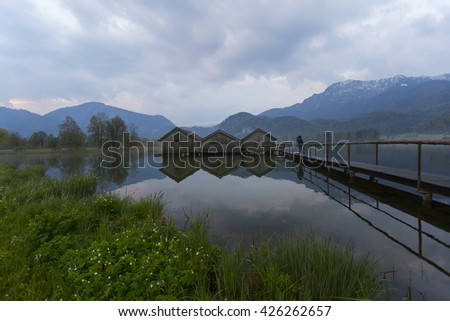 GERMANY -Kochelsee ; 01 MAY 2016  ,Boathouses at lake Kochelsee with snow-covered mountains in background, Schlehdorf, Bavaria, Germany