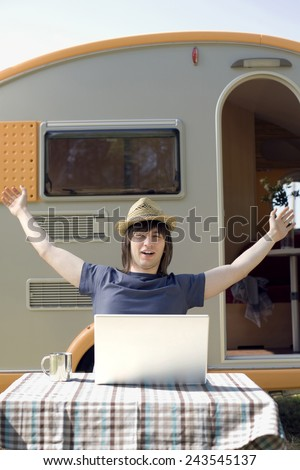Germany, Leipzig, Ammelshainer See, Young man using laptop, camping trailer in background