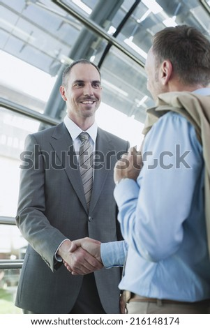 Germany, Leipzig-Halle, Airport, two businessmen shaking hands - stock photo