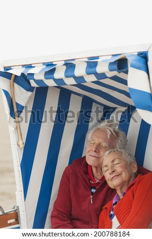 Germany, North Sea, St.Peter-Ording, Senior couple resting on hooded beach chair - stock photo