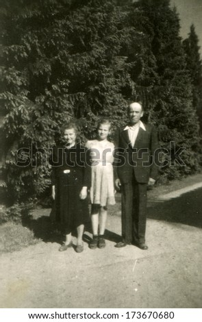 GERMANY, ROSTOCK - 1940s: An antique photo shows man and woman standing together with her teenage daughter on the footpath in the park