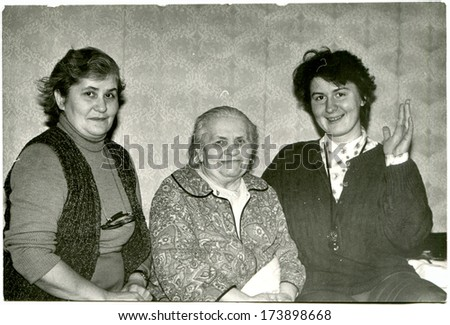 GERMANY - 1960s: An antique photo shows three women of different generations sitting on the bed