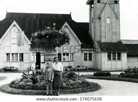 GERMANY -  1950s: An antique photo shows woman with  boy on the background of flowerbed and house