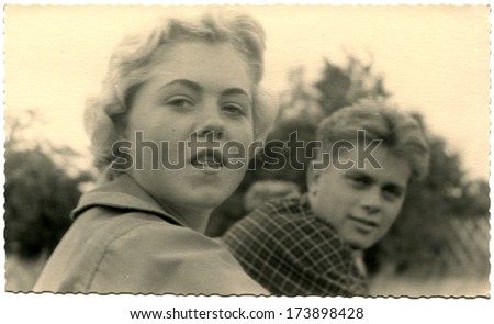 GERMANY - 1950s: An antique photo shows young girl and boy looking into camera - stock photo