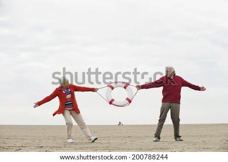Germany, St Peter-Ording, North Sea, Senior couple pulling lifesaver on beach - stock photo